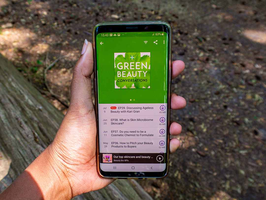 Person holding phone. Green beauty podcasts